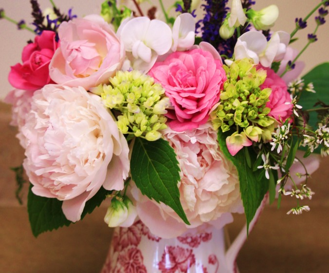 A traditional arrangement in a transferware pitcher:  the lime green unopened hydrangea, dark green hydrangea leaves and rich purple lavender ground the soft pinks of roses and peonies, while the pitcher gives the arrangement a classic feeling.